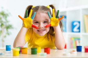 little girl in yellow shirt with brightly painted hands smiling at camera
