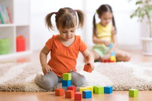 two toddler girls playing with blocks sitting on a rug