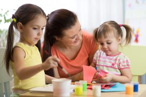 woman sitting with and smiling at two young girls as they do arts and crafts