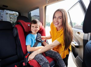 Mother with son in car seat
