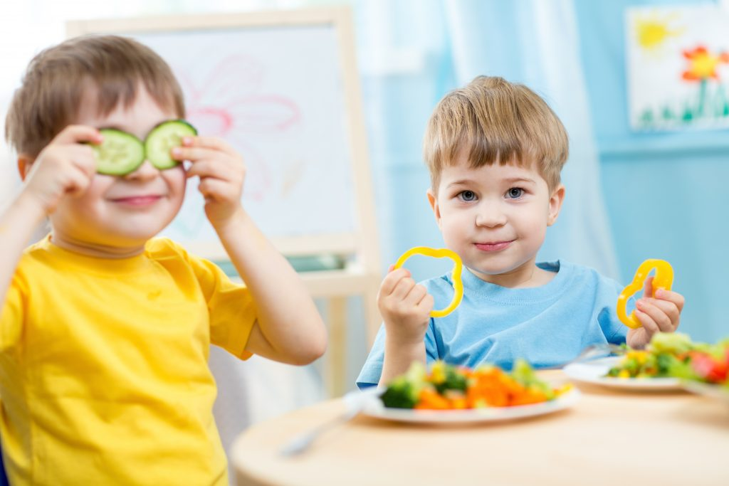 two toddler boys sitting at a table eating vegetables